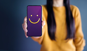 Customer Experience Concept, Happy Woman Show Smiley Face for her Satisfaction on Smart Phone